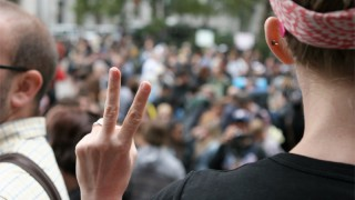 Photo of a man putting up the peace sign in front of the Occupy Wall Street crowd.