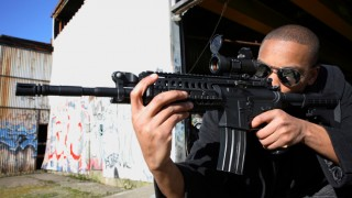 Young man with shaved head and shades aiming an assault rifle in a graffitied neighborhood