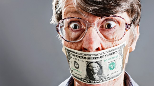 Old furious woman who has been gagged with dollar bills